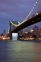 """Brooklyn Bridge Illuminated at Night, New York City, New York State, USA....Waterfall installed under the bridge as part of """"The New York City Waterfalls"""" project by Danish-Icelandic artist Olafur Eliasson.  This waterfall, along with three others, nearby in New York City's East River, ran from June 26 to October 13 2008, as part of an artistic project by Olafur Eliasson, presented by the Public Art Fund in collaboration with The City of New York."""