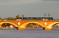 The old Pont de Pierre bridge in Bordeaux on the Garonne River with the modern new tram passing over it