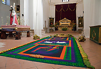 Antigua, Guatemala.  An alfombra (carpet) of colored sawdust, bounded with mangos, coconuts, and bread, in the Cathedral of San Jose (Santiago), during Holy Week, La Semana Santa.