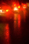 A wet road at night with stopped cars, tail lights on