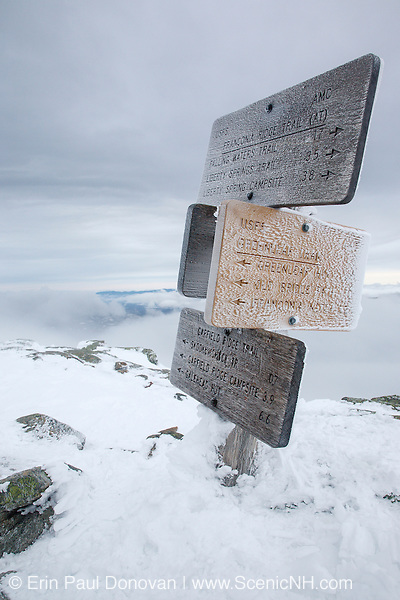 Trail sign on the summit of Mount Lafayette covered in snow during the winter months in the White Mountains, New Hampshire. The Appalachian Trail (Franconia Ridge Trail) travels of the summit of this mountain.