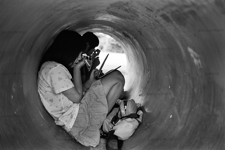 Girls make up in the abandoned concrete tube for construction in a park in Matsumoto, Nagao.<br /> <br /> Des filles se maquillent dans un tube de béton abandonné pour la construction dans un parc de Matsumoto, Nagao.