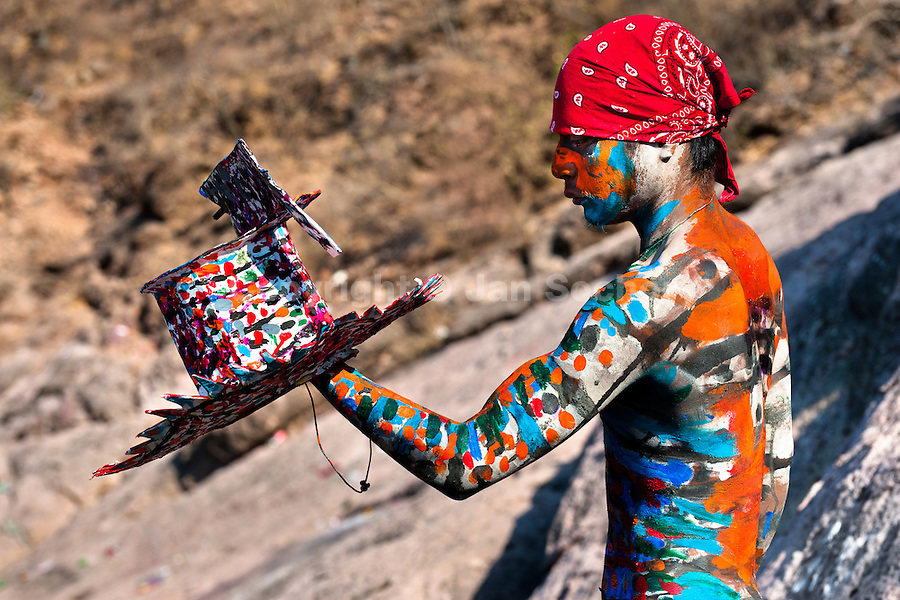 """A Cora Indian boy, with body and face painted colorfully, paints his multi-colored hat before the religious ritual ceremony of Semana Santa (Holy Week) in Jesús María, Nayarit, Mexico, 22 April 2011. The annual week-long Easter festivity (called """"La Judea""""), performed in the rugged mountain country of Sierra del Nayar, merges indigenous tradition (agricultural cycle and the regeneration of life worshipping) and animistic beliefs with the Christian dogma. Each year in the spring, the Cora villages are taken over by hundreds of wildly running men. Painted all over their semi-naked bodies, fighting ritual battles with wooden swords and dancing crazily, they perform demons (the evil) that metaphorically chase Jesus Christ, kill him, but finally fail due to his resurrection. La Judea, the Holy Week sacred spectacle, represents the most truthful expression of the Coras' culture, religiosity and identity."""
