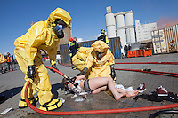 "Paramedics in HAZMAT (hazardous material) suits hose down a ""victim"" supposedly exposed to chemicals. HarbourEx15, a field training exercise with scenarios connected to operations in the harbor April 27th – 29th 2015.<br />