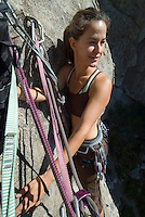 Smiling woman standing on tiny ledge at belay station while rock climbing at Castle Rocks, Idaho