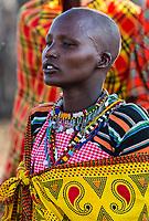Tanzania. Maasai Woman in Traditional Dress Singing to Welcome Visitors.  Maasai Village of Ololosokwan, Northern Serengeti.