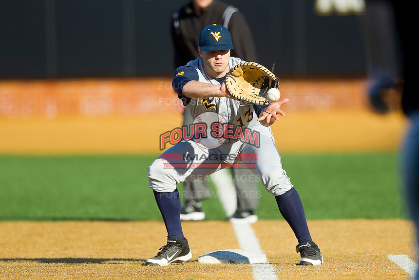 West Virginia Mountaineers first baseman Ryan McBroom (13) fields a ground ball in foul territory during the game against the Wake Forest Demon Deacons at Wake Forest Baseball Park on February 24, 2013 in Winston-Salem, North Carolina.  The Demon Deacons defeated the Mountaineers 11-3.  (Brian Westerholt/Four Seam Images)