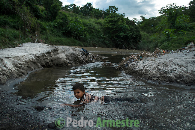 """November 07, 2014. """"Water it´s the real thing""""<br /> Anderson Salguero swims in a river contaminated called Acelhuate (Nejapa, El Salvador). Anderson and his family have to walk near two hours to get the river because they don´t have water at home.<br /> The people of Nejapa in El Salvador, have no drinking water because the Coca -Cola company overexploited the aquifer in the area, the most important source of water in this Central American country. This means that the population has to walk for hours to get water from wells and rivers. The problem is that these rivers and wells are contaminated by discharges that makes Coca- Cola and other factories that are installed in the area. The problem can increase: Coca Cola company has expansion plans, something that communities and NGOs want to stop. To make a liter of Coca Cola are needed 2,4 liters of water. ©Calamar2/ Pedro ARMESTRE"""