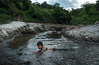 "November 07, 2014. ""Water it´s the real thing""<br /> Anderson Salguero swims in a river contaminated called Acelhuate (Nejapa, El Salvador). Anderson and his family have to walk near two hours to get the river because they don´t have water at home.<br /> The people of Nejapa in El Salvador, have no drinking water because the Coca -Cola company overexploited the aquifer in the area, the most important source of water in this Central American country. This means that the population has to walk for hours to get water from wells and rivers. The problem is that these rivers and wells are contaminated by discharges that makes Coca- Cola and other factories that are installed in the area. The problem can increase: Coca Cola company has expansion plans, something that communities and NGOs want to stop. To make a liter of Coca Cola are needed 2,4 liters of water. ©Calamar2/ Pedro ARMESTRE"