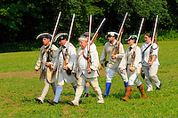 Colonial provincial troops, loyal to Britain, march from the battlefield after a skirmish with militiamen during a Revolutionary War reenactment at the Nathan Hale Homestead, Coventry, Connecticut, USA...