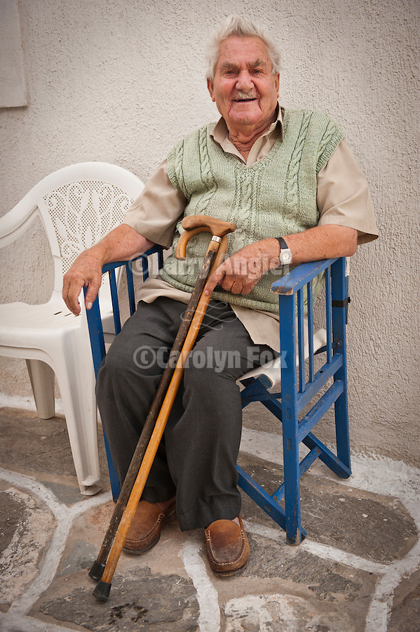 Old man with canes in blue chair, Naoussa, Greece.