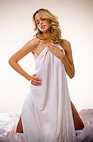 Blonde woman draped in bedsheet .