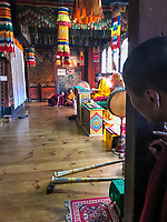Bumthang, Bhutan.  Looking in on a   Monk Reciting Prayers in Jambay Lhakhang temple.