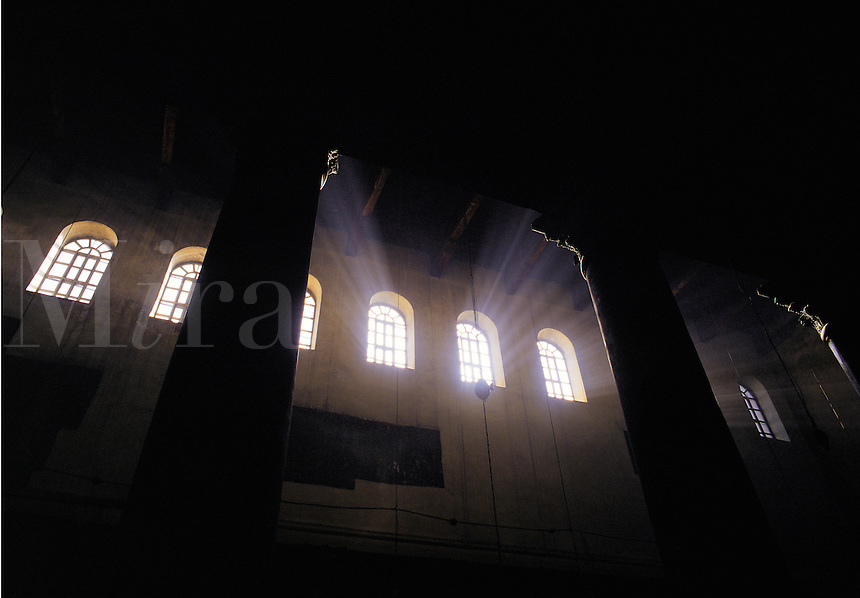 Light streams through high arched windows into the dark interior of the Church of the Nativity in Bethlehem, Israel. The Church is believed to have been built on Jesus' birthplace