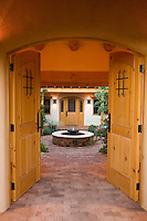 Brick path entry through wooden doors into New Mexico inner courtyard garden room sanctuary with fountain