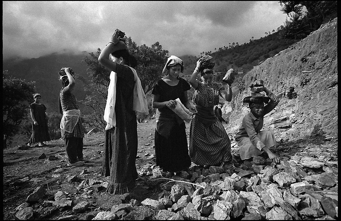 """Residents from the surrounding region work on construction of the Maoist rebel """"Martyr's Road"""" on the section linking the villages of Nuwagau and Tila, in the Rolpa district of Nepal on 23 June, 2005. The road is build entirely by hand, mostly by forced labor of local residents who were told by the Maoists to give one person per household for a 15 day shift of work.<br />"""