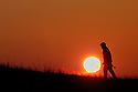 00105-044.10 Bowhunting: Archery carrying bow is silhouetted as he hunts on the prairie.  Orange, sunset, sunrise.  H1L1
