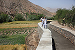 13 June 2013, Onaba Village, Onaba District, Panjshir Province,  Afghanistan.  Local village men Ahmad Zia (left) and Najibullah Alimi walk along the wall of the irrigation canal they have built alongside the Panjshir River at their village of Onaba in Onaba District. The water is used to feed their crops which is wheat at the moment.  Canals are being built and rehabilitated under the Irrigation Restoration and Development Project (IRDP). While some donors are supporting reconstruction/development of specific rivers the Emergency Irrigation Rehabilitation Project (EIRP) is instrumental in the Govt of Afghanistan's launch of a national irrigation scheme. Typical rehabilitation works would include improving canal intake structures, conveyance channels and aqua ducts. Picture by Graham Crouch/World Bank