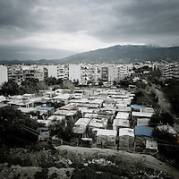 A refugee shantytown next to citizens' housing in the port of Patras. Patras is home to about 3,000 illegal immigrants. Most of them are Afghans, although there are also some Iranians and Uzbeks. They stop in Patras to try and find passage to various European destinations by hiding in ships, containers and trucks parked in the port. If they are lucky they will make it to their destination. However some of them have been living in the camp for the last 6 months and a few have been there for years. Many of them live in shacks made from cartons, plastic and wood they found on the beach. To shelter from the cold they also squat in abandoned buildings, living without water and electricity. The living conditions are inhumane and unhygienic.
