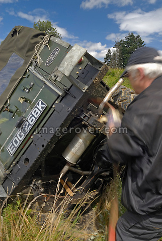 Fixing a recovery strap to a Land Rover Series 2a Lightweight which lies on its side after it slipped off the track into a ditch, Bining, France. --- No releases available. Automotive trademarks are the property of the trademark holder, authorization may be needed for some uses.