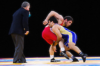 11 DEC 2011 - LONDON, GBR - Soslan Ktsoev (RUS) (in blue) takes advantage of his position at the start of an overtime period in the men's 84kg category final against Sharif Sharifov (AZE) (in red) at the London International Wrestling Invitational and 2012 Olympic Games test event at the ExCel Exhibition Centre in London, Great Britain .(PHOTO (C) NIGEL FARROW)