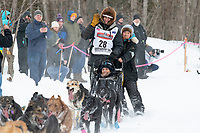 Robert Redington and team run past spectators on the bike/ski trail near University Lake with an Iditarider in the basket and a handler during the Anchorage, Alaska ceremonial start on Saturday, March 7 during the 2020 Iditarod race. Photo © 2020 by Ed Bennett/Bennett Images LLC