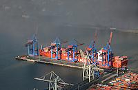Containerschiff der Reederei Hamburg Sued am Burchardkai: EUROPA, DEUTSCHLAND, HAMBURG, (EUROPE, GERMANY), 11.11.2012 Der HHLA Container Terminal Burchardkai ist die groesste und aelteste Anlage fuer den Containerumschlag im Hamburger Hafen. Hier, wo 1968 die ersten Stahlboxen abgefertigt wurden, wird heute etwa jeder dritte Container des Hamburger Hafens umgeschlagen. 25 Containerbruecken arbeiten an den Tausenden Schiffen, die hier jaehrlich festmachen, und taeglich werden mehrere Hundert Eisenbahnwaggons be- und entladen. Mit dem laufenden Aus- und Modernisierungsprogramm wird die Kapazitaet des Terminals in den kommenden Jahren schrittweise ausgebaut. Am nordwestlichsten Punkt liegt ein Containerschif der Reederei Hamburg Sued. Die Elbe hat etwas Nebel