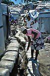 """A woman cleans a drainage canal in the largest """"tent city"""" of Haitian earthquake survivors, located on a former nine-hole golf course in Port-au-Prince. The Petionville Club is host to more than 44,000 people."""