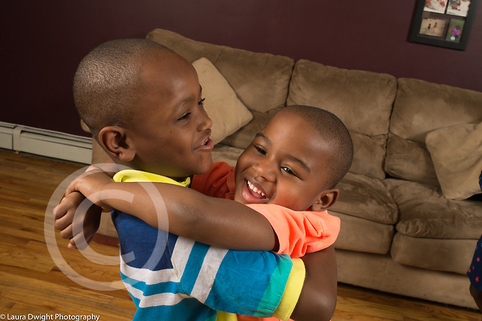 4 year old boy at home hugging older male cousin