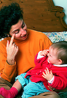 Mother and infant child interact pointing at the eye