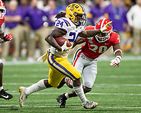 ATLANTA, GA - DECEMBER 7: Chris Curry #24 of the LSU Tigers avoids a tackle by J.R. Reed #20 of the Georgia Bulldogs during a game between Georgia Bulldogs and LSU Tigers at Mercedes Benz Stadium on December 7, 2019 in Atlanta, Georgia.