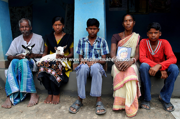 Monika Besra (42) and her family posing for a photograph at her house in Danagram, a village 40 kms away from Malda Town,  West Bengal, India. 20th August 2010.  Monica Besra says that her non curable tumour got cured on the first annivarsary of Mother Teresa's death by putting a Mother Teressa Medellion on the swollen part of her abdomen, which was recognized by the Vatican in the year 2002 and started the process of Mother Teresa's beatification, a major step towards sainthood.