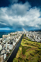 An aerial view of Ala Wai Golf Course and Canal and Waikiki with a big rainbow touching down around Ward Avenue on O'ahu.