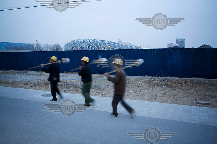 Workers from the construction site of the Beijing 2008 Olympic Games National Stadium, also known as the Bird's Nest, finishing their shift.