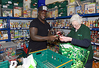 Adebayo Akinfenwa of Wycombe Wanderers - How the strongest man in football is spreading the Christmas cheer. <br /> <br /> Interview and feature will be shown on Sky Sports News HQ and across Sky Sports digital platforms Christmas Day.<br /> <br /> Bayo Akinfenwa helps out volunteer Ann at the Food Bank in Lewisham, England on 23 December 2016. <br /> <br /> Photo by Alan  Stanford / PRiME Media Images.