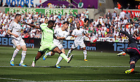 Kelechi Iheanacho of Manchester City (2nd L) is challenged by Jack Cork of Swansea City as Kristoffer Nordfeldt of Swansea City dives (R) to catch the shot during the Swansea City FC v Manchester City Premier League game at the Liberty Stadium, Swansea, Wales, UK, Sunday 15 May 2016