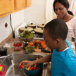 Mother in kitchen with 10 year old son, food preparation, boy washing stawberry at sink