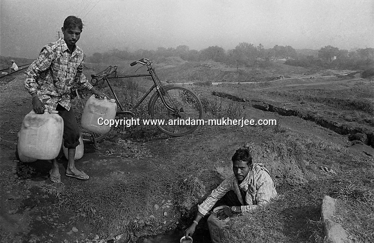 Men collecting dringking water from a natural spring as Jharia suffers from scarcity of clean unpolluted water, Jharia, Jharkhand, India. Arindam Mukherjee