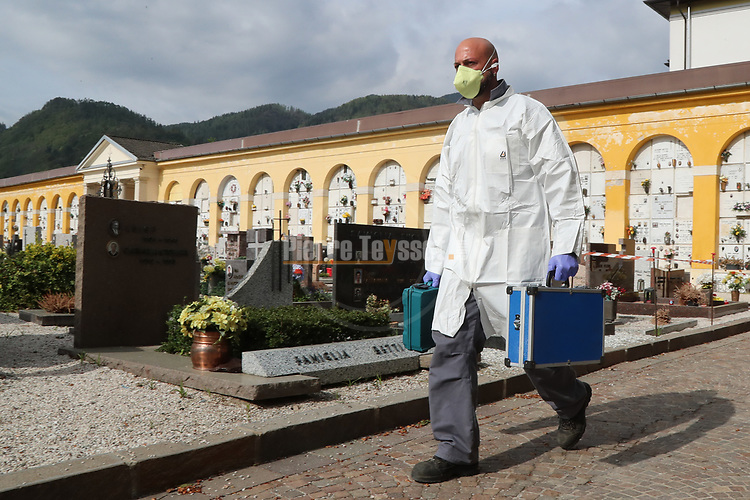 Europe Virus Outbreak - Cemetery Works in Pergine Valsugana, Italy on April 21, 2020. A sweeping lockdown is in place in Italy to try to slow down the spread of coronavirus pandemic. An employee wearing gloves and masks walks with small suite cases to treat a coffin.