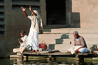 HINDU MEN PRAY and perform spiritual ablutions by the side of the GANGES RIVER - VARANASI (BENARES), INDIA