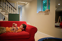 """Jack Ursitii, age 7, plays on a couch during a """"sensory break"""" in his home in Dover, Mass., on Monday, July 25, 2011.  Jack has been diagnosed with autism.  After school at his home, Jack works with his teacher and a therapist to do educational and independent leisure activities. Periodically Jack takes """"sensory breaks"""" to stop activity and play independently, allowing him to return to his tasks with greater concentration. During the """"sensory breaks"""" Jack does a variety of things, including looking at his reflection, making faces, jumping on a small trampoline or cushions, or play with an iPad...Jack Ursitti wears a small GPS ankle bracelet at all times in case he runs off from his family or caretakers. The device will be activated if he goes missing, allowing police and other searchers to find him."""