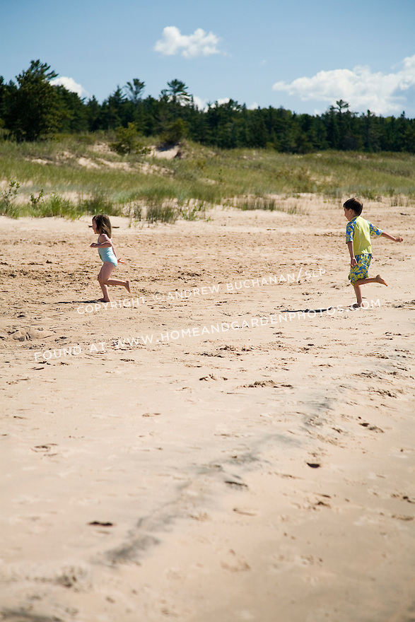 long view of two kids, 3 year old girl & 6 year old boy, chasing each other on sandy beach with dunes and dune grass behind