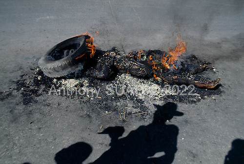 Port-au-Prince, Haiti<br /> November 25, 1987<br /> <br /> The remains of a suspected ton-ton-macoute prior to elections to be held on November 29th,  the first attempt at a democratic election in Haiti. It was unsuccessful as 34 people were killed at a polling station and elections were moved up to February 1988.<br /> <br /> Leslie François Manigat won the election with many political parties boycotting. He had military backing but once in office he sought greater control over the military in an effort, to fight corruption. Manigat's government was overthrown by General Henri Namphy within months.