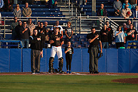 """Batavia Muckdogs catcher Jared Barnes (26) stands with a """"Star of the Game"""", as well as umpires Evin Johnson (left) and Marcelo Alfonzo (right), during the national anthem before a game against the Auburn Doubledays on August 26, 2017 at Dwyer Stadium in Batavia, New York.  Batavia defeated Auburn 5-4.  (Mike Janes/Four Seam Images)"""