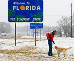A man plays with his dog in the snow in Florida on US 231 at the Alabama State line south of Dothan February 12, 2010.