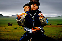 """Rowan, a five-year-old autistic child, on horseback with six-year-old Bodibilguunson, the son of a guide, during a horseback expedition across Mongolia. Rowan, who has been nicknamed """"The Horse Boy"""", embarked on a therapeutic journey of discovery with his parents to visit a succession of shaman healers in one of the most remote regions in the world. Following Rowan's positive response to a neighbour's horse, Betsy, and some reaction to treatment by healers, Rowan's parents hoped that the Mongolian shamanistic rituals along the route and the prolonged contact with horses would help to unlock their son's autism and assist his development.."""