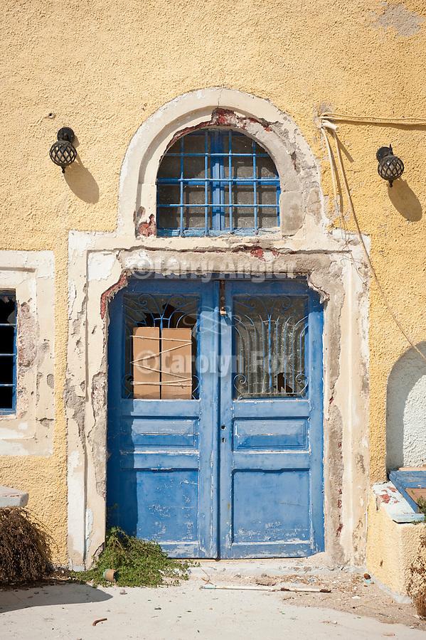 Blue double-door, yellow wall and arch, Fira, Santorini, Greece.