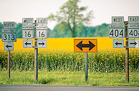 Road signs with arrows pointing in east and west directions.