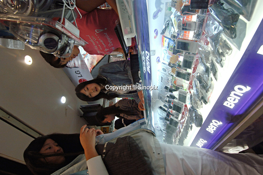 "Two female shopper browsing BenQ digital cameras in a computer plaza in Chengdu, China. Chengdu is the capital of China's most populous province, land-locked Sichuan. The capital city is seeing massive investment of capital as it has modelled itself as the gateway to the western China which the Chinese government are trying to encourage invetement with its ""Go West"" campaign.."