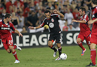 WASHINGTON, DC. - AUGUST 22, 2012:  Dwayne DeRosario (7) of DC United balances over the ball in between  Austin Berry (22) and  Daniel Paladini (11) of the Chicago Fire during an MLS match at RFK Stadium, in Washington DC,  on August 22. United won 4-2.